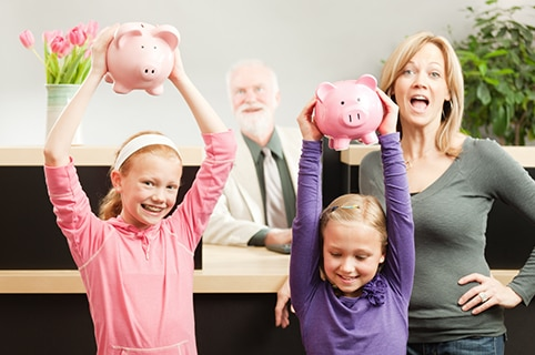 two young girls holding piggy banks with their mom at a bank