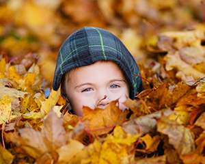 Photo of a child laying in a pile of fallen leaves