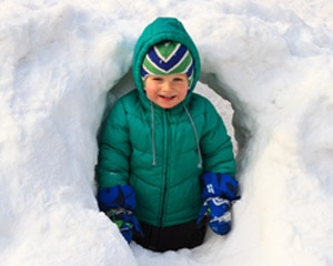 Small child playing inside homemade igloo