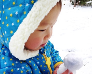 Small child holding snow ball