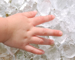 Child's hand touching ice